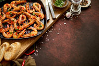 Grilled prawns in cast iron grilling pan with fresh lemon, parsley, chili, garlic white wine sauce