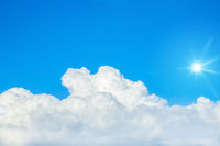 typical blue sky with sun and clouds background