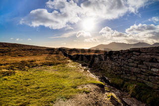 Mourn Wall on the bank of Slieve Donard mountain with blue sky, white clouds and sunrays.