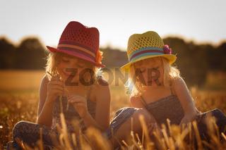 Zwei junge Maedchen spielen sitzend im Feld