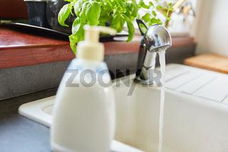 Flüssigseife neben Wasserhahn mit Wasser in Küche