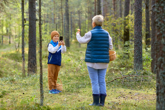 grandson photographing grandmother with mushroom