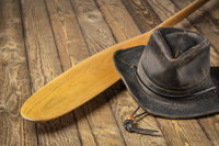 wooden canoe paddle and hat