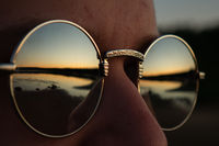Reflection in the glasses of the coast and sunset.