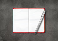 Red open lined notebook with a pen isolated on dark concrete background