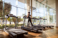 Woman running on treadmill in gym. Ealthy lifestyle.
