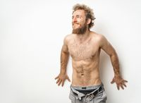 Shirtless handsome tattooed young guy with beard and curly hair wearing unbuttoned denim jeans with underwear under looking sideways isolated on white background