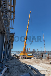 A large yellow truck crane stands ready to work on the construction site