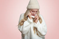 Woman in white knitted sweater on pink bakcground