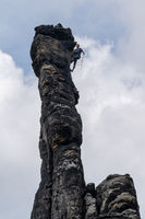 rock climbers rappelling from the  top of a rock pillar in the Elbsandstone mountains in Saxon Switzerland