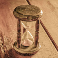 Time concept. A vintage hourglass with sand falling through, on a rustic background, toned square image