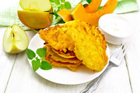 Pancakes of pumpkin with apple in plate on wooden board
