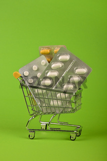 Several blister packs of pills in shopping cart