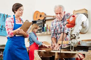 Frau macht Lehre im Handwerk bei Gitarrenbauer