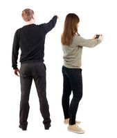 Back view of couple in sweater with mobile phone.