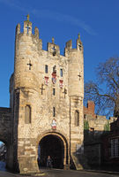 a close up of the of Micklegate Bar the 12 century gatehouse and southern entrance to the city of york with a cyclist passing under the arch