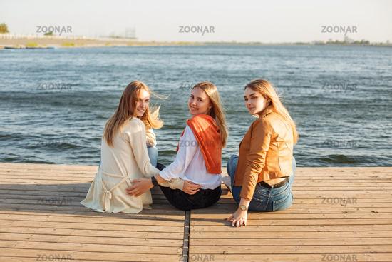 Happy girlfriends resting on pier near water