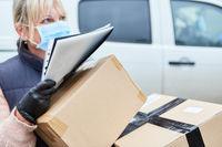 Paketbotin mit Mundschutz bei der Zustellung von Paketen