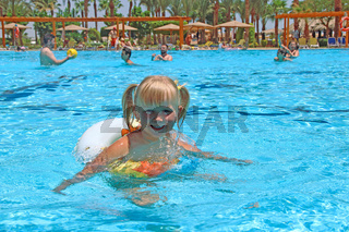 smiling baby girl with nice plaits swimming in pool lying on inflatable circle