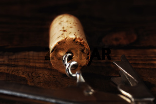 Closeup of a wine cork and corkscrew on a dark wood table, with strong side light. Shallow depth of field with focus on the end of the cork.