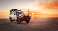 Western Australia – Outback adventure with 4WD car at the beach of an ocean at sunrise and a bloodred sky