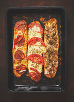 Delicious hot sandwich baguettes baked with tuna, cheese, tomatoes, olives, courgette and mushrooms
