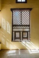 Interleaved wooden ornate window - Mashrabiya - in stone wall
