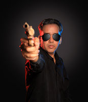 Indian Man with sunglasses and gun on dark background