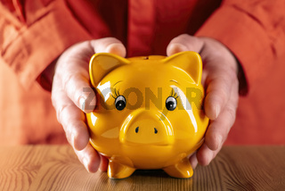 Hände umfassen ein gelbes Sparschwein
