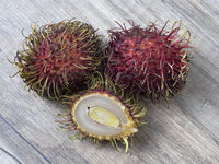 Rambutan whole and a half on a wooden background.