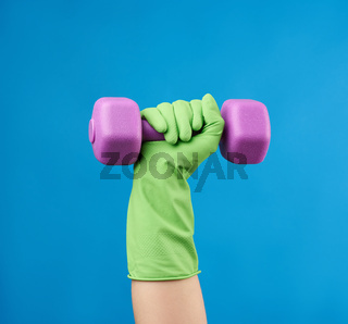 female hand holds a plastic pink dumbbell on a blue background