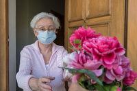 Seniorin mit Mund- Nasenschutz bekommt Blumen an der Haustür