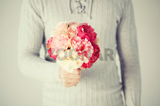 man holding bouquet of flowers