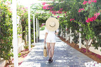 Blond girl in straw hat in front of pink bougainvillea flowers