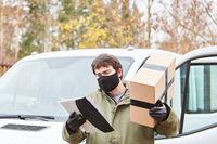 Lieferdienst Paketbote mit Mundschutz bei der Arbeit