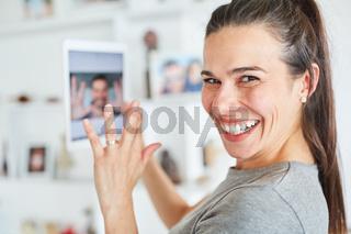 Glückliche Frau mit Tablet beim Videochat online