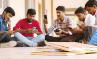 selective focus of Books, Group of students busy on mobile by avoiding books during exams at college - Teenager students on smartphone video game addiction concept.