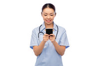 happy asian female doctor or nurse with smartphone