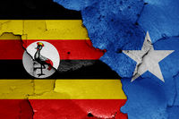 flags of Uganda and Somalia painted on cracked wall