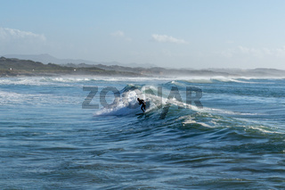 surfer enjoying a surf session at Sao Torpes Beach in Sines on the Alentejo Coast