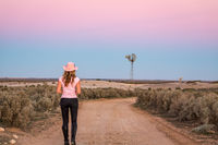 Walking along dirt road of vast open spaces of outback