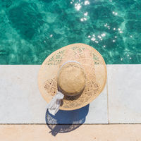 Woman wearing big summer sun hat relaxing on pier by clear turquoise sea.