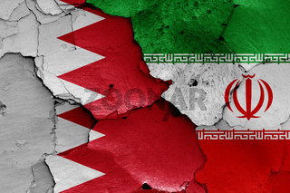 flags of Bahrain and Iran painted on cracked wall