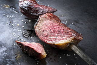 Barbecue dry aged wagyu Brazilian picanha from the sirloin cap of rump beef sliced and offered as close-up on a skewer on a rustic old board with copy space