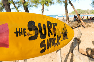Yellow surfboard sign leading to the surf shack