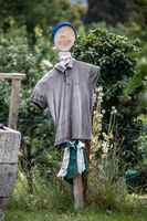 funny scarecrow with clothes in the garden