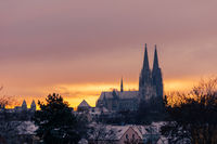 The cathedral St. Peter in Regensburg on cold winter morning in December with fresh snow on the roofs and spires
