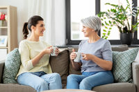 senior mother and adult daughter drinking coffee
