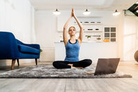 White caucasian woman do sit yoga at home from online tutorial