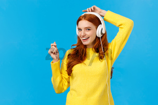 Cheeky and joyful, happy smiling redhead ecstatic woman having fun, listen music and lifting hands up as dancing, enjoying awesome sound quality, standing blue background delighted